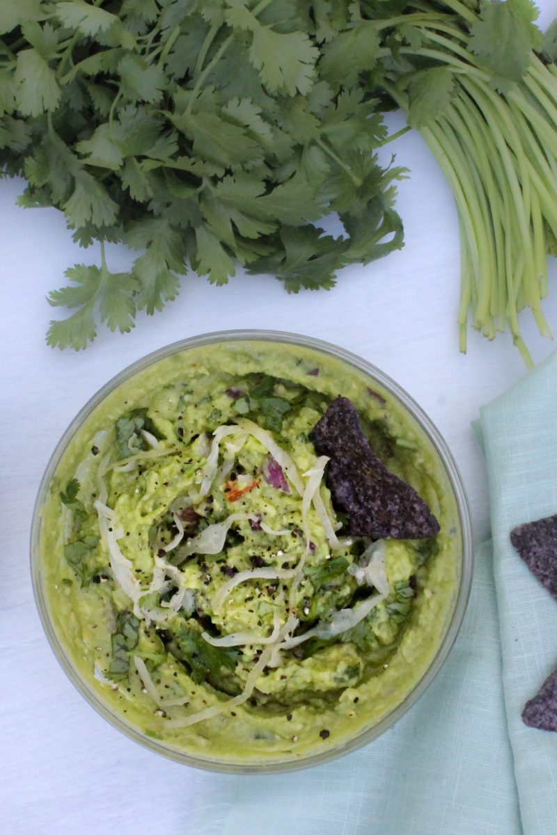 guacamole in a bowl topped with sauerkraut and cilantro