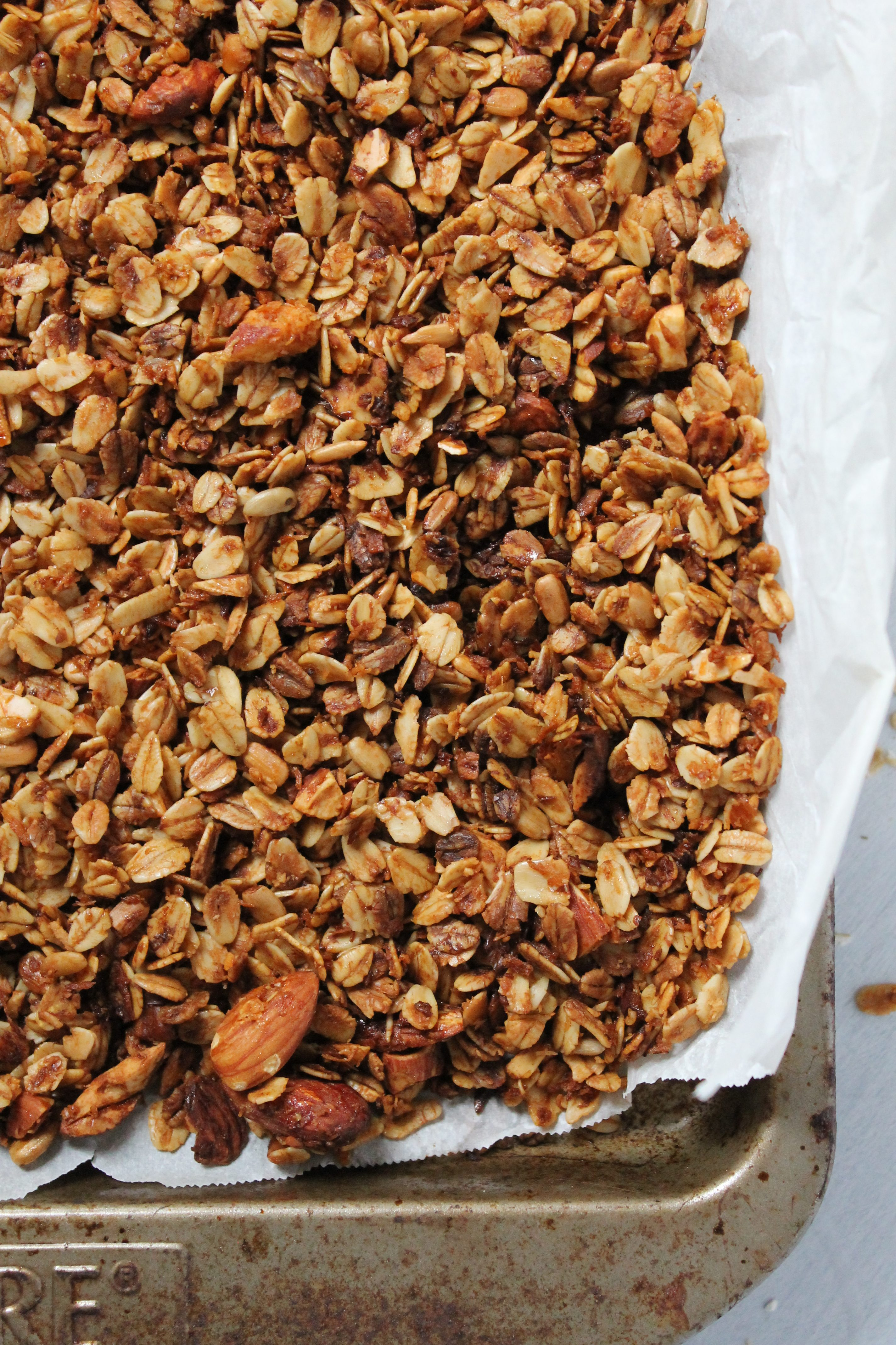 homemade granola with almonds on a sheet pan