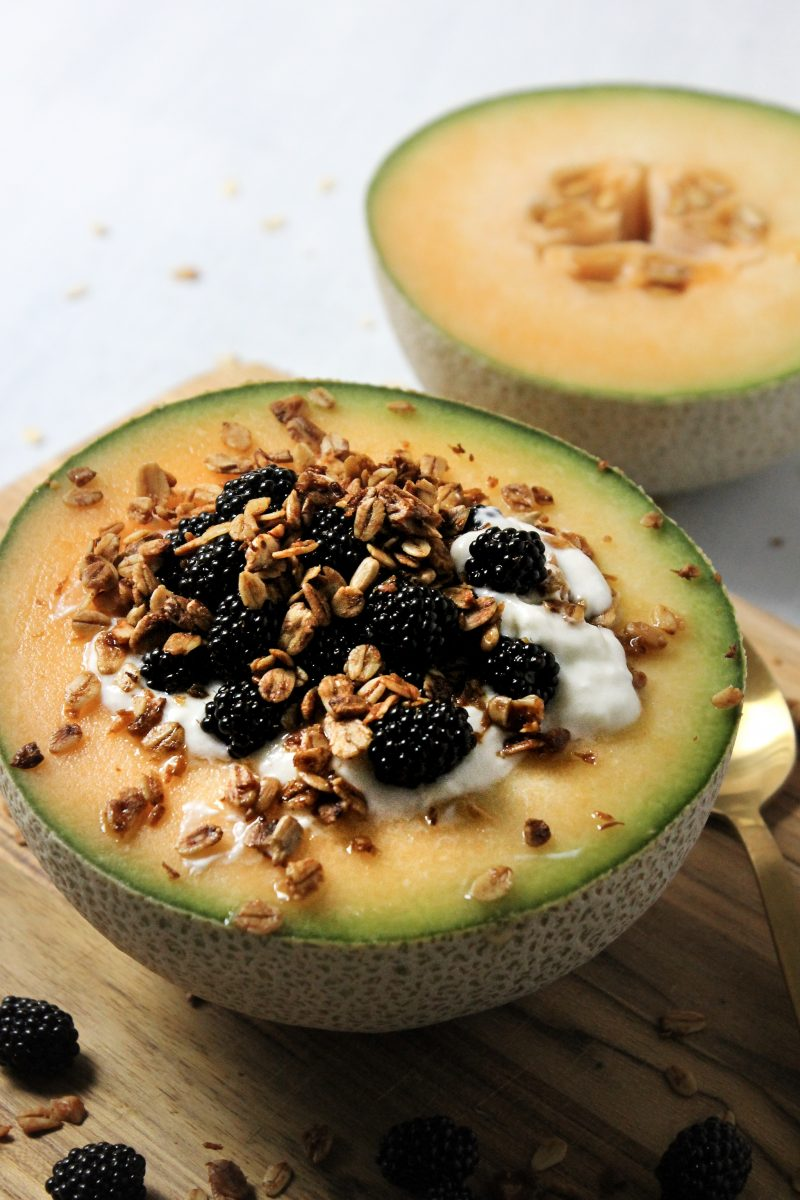 cantaloupe filled with yogurt, granola, and blackberries.