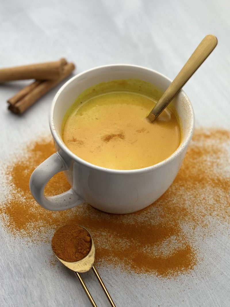 a mug filled with warm milk, bright orange turmeric, and other spices.