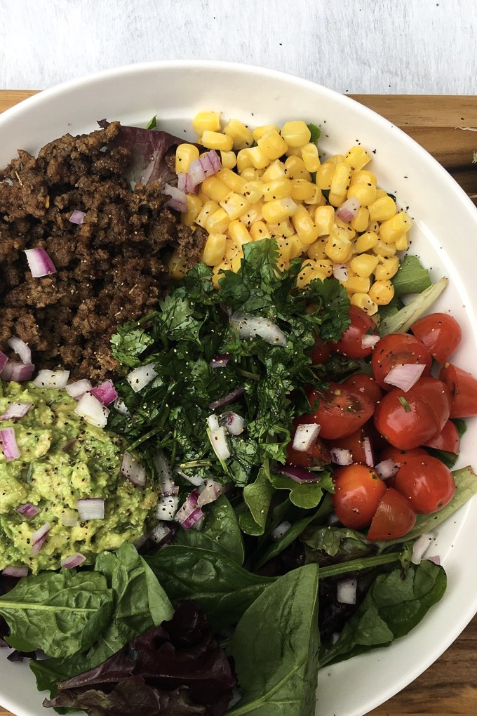 a bowl filled with spring mix. ground beef and spices, mashed avocado, corn, tomato, cilantro, and red onion.